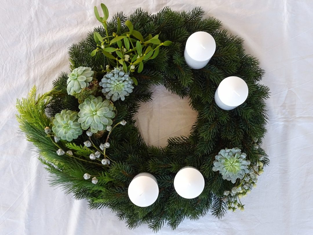 Asymmetrischer DIY-Adventskranz mit Sukkulenten, Mistelzweigen, Moos, Eukalyptusbeeren, Tanne, Fichte und Thuja als echter Hingucker